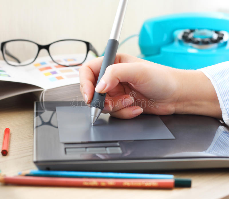 Grafico che lavora nell'ufficio con la penna della compressa fotografia stock