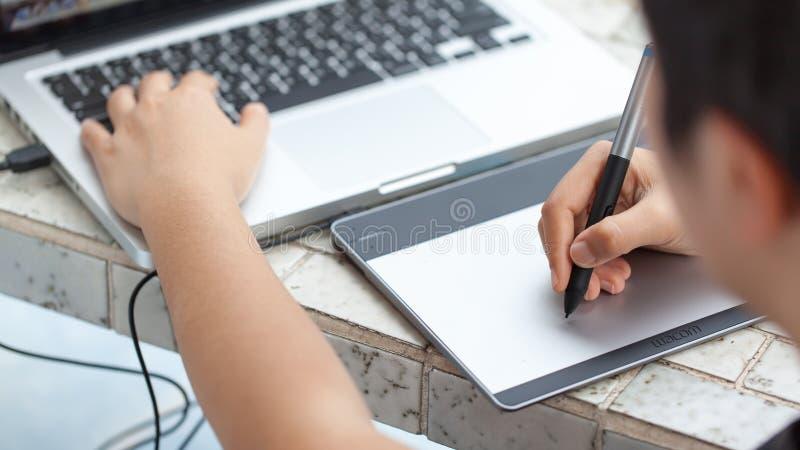 Grafico che per mezzo della compressa digitale e del computer a casa offic immagini stock libere da diritti