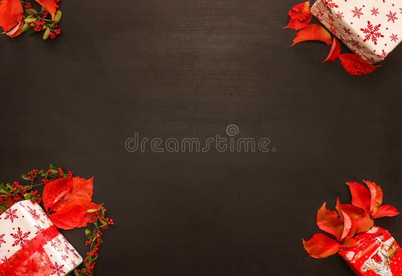 Grafico del fondo di Natale Presente, leafes rossi Superficie di legno fotografia stock