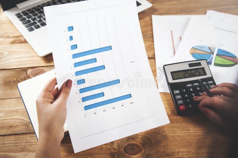 Grafico della mano della donna con il calcolatore sulla tavola fotografia stock libera da diritti