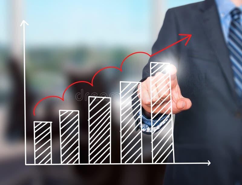 Grafico di crescita del disegno della mano dell'uomo d'affari sullo schermo visivo fotografie stock