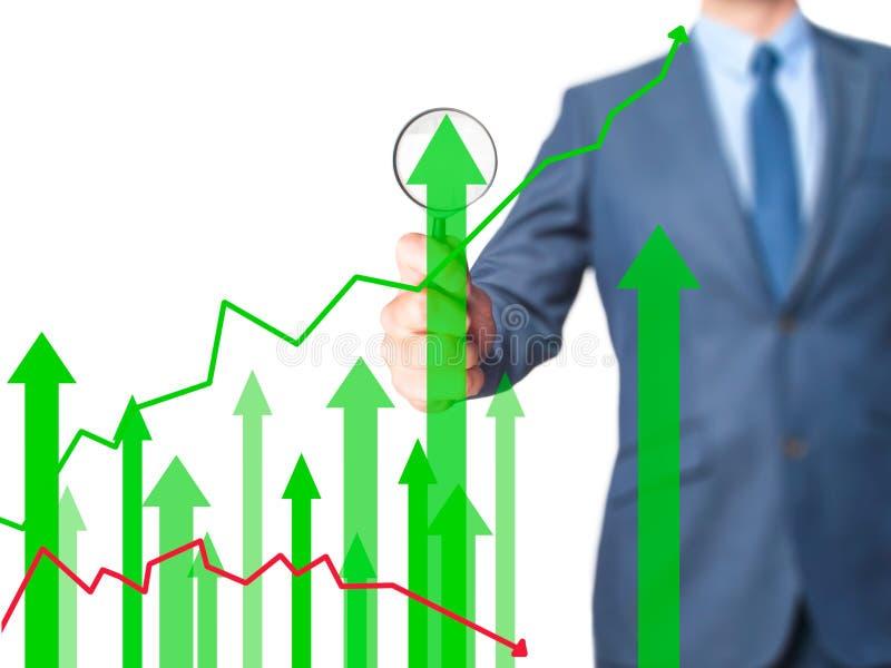 Grafico di crescita di vendite - lente d'ingrandimento della tenuta dell'uomo di affari su Sc immagini stock