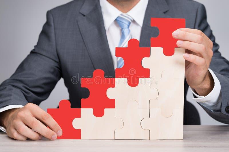 Grafico di Holding Red Jigsaw dell'uomo d'affari sulla Tabella fotografia stock