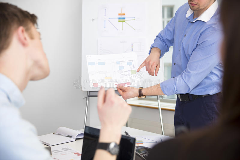 Grafico di mostra professionale ai colleghi in ufficio fotografie stock libere da diritti