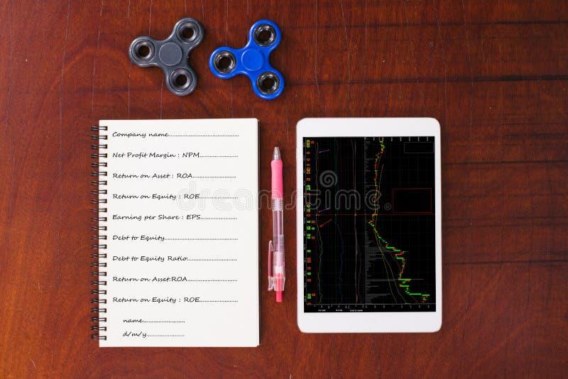 Grafico di riserva sulla compressa, penna, filatore della mano, taccuino sulla tavola di legno fotografia stock