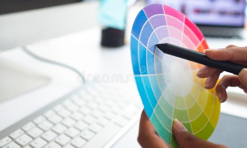 Grafico femminile che lavora con il campione di colore allo scrittorio in un ufficio moderno fotografie stock