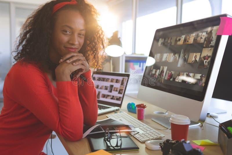 Grafico femminile con le mani sul mento che esamina macchina fotografica mentre sedendosi allo scrittorio fotografia stock libera da diritti