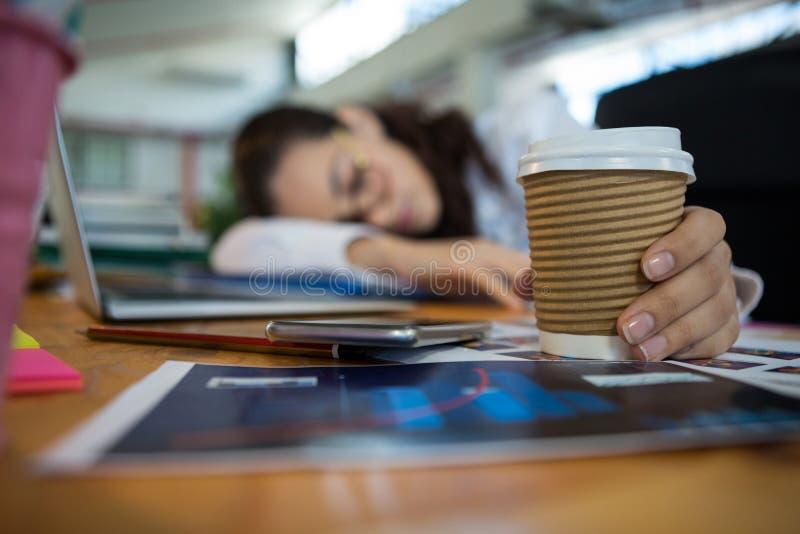 Grafico femminile stanco che tiene tazza eliminabile mentre dormendo sullo scrittorio fotografia stock