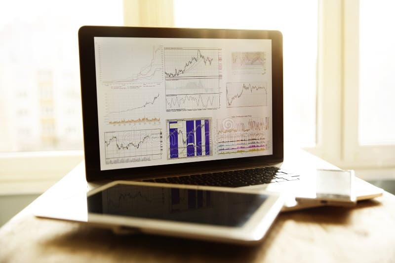 Grafico finanziario sullo schermo del computer portatile e della compressa fotografie stock