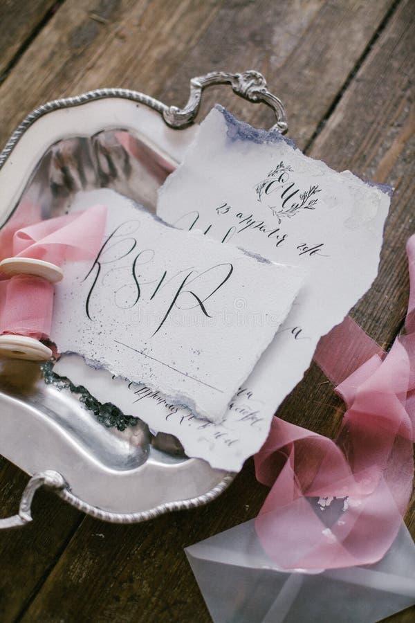 Grafik av härliga bröllopkalligrafikort och silverplattan med det siden- bandet royaltyfria foton
