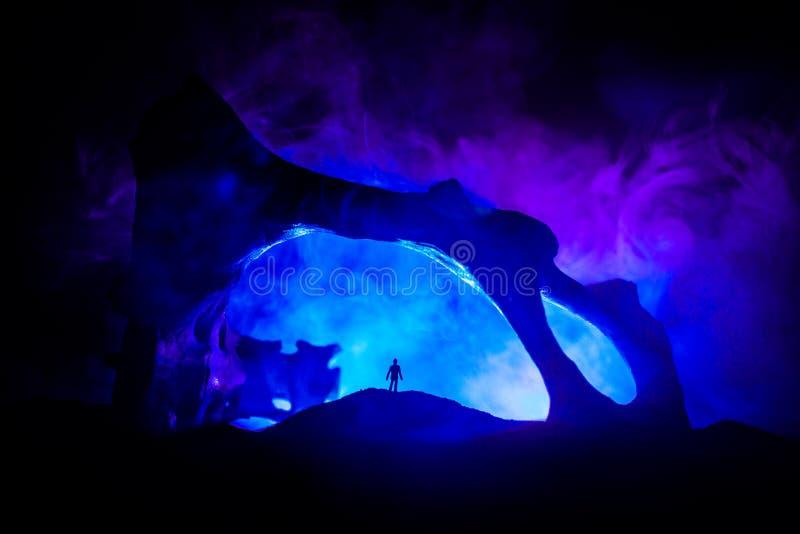 Grafikdekoration mit dem Tierknochen Schattenbild in einer verlassenen Untertagekrypta Mann, der vor einem H?hleeingang steht stockbilder