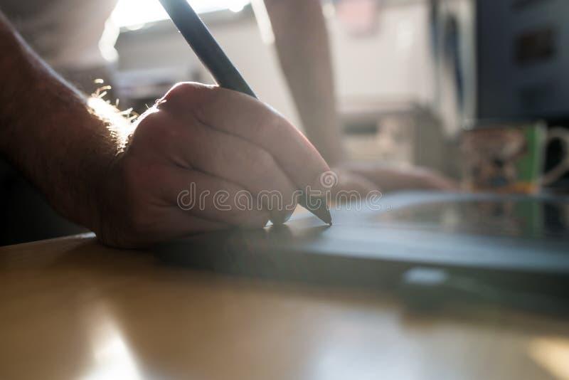 Grafikdesigner oder der Fotograf, der eine Tablette und einen Griffel verwendet, sperren t ein stockfotos