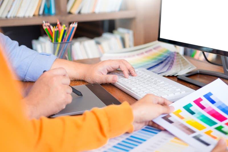Grafikdesignpartner, die Erneuerungs- und Technologiekonzept auf einem Tischrechner und einer Auswahl zusammenarbeiten stockfotos