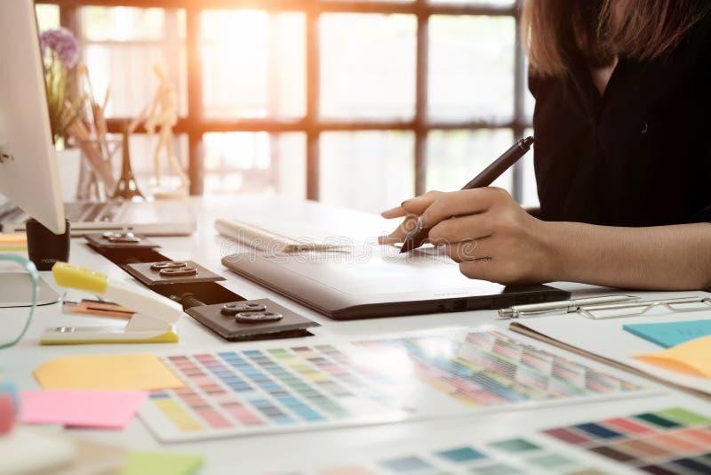 Grafikdesignschreibtischhand unter Verwendung des Mäusewannen-Skizzengerätes auf creati stockbild