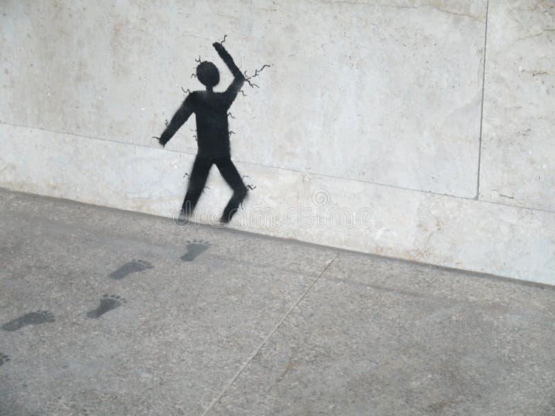 Grafikmalerei auf dem grauem Stein/Mann, die durch Steinwand laufen stockbild