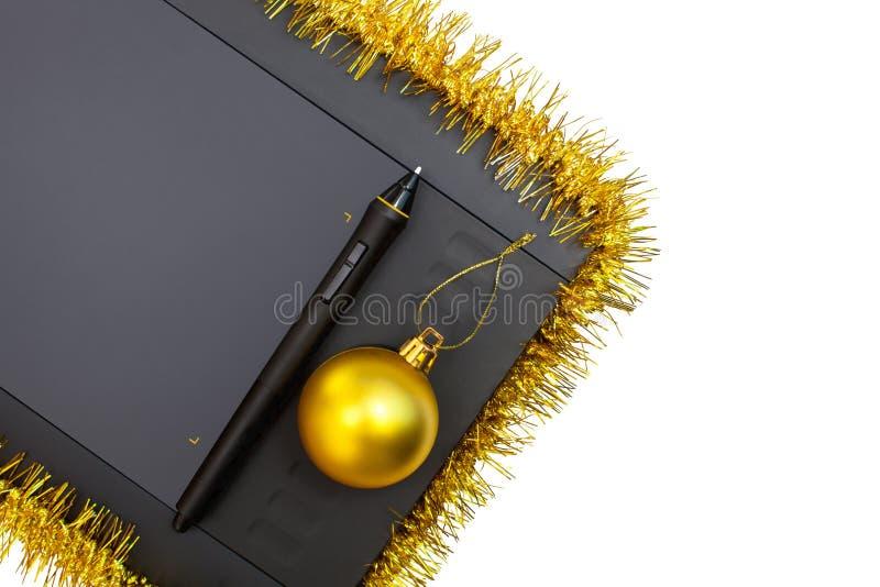 Grafiktablette mit dem Griffel verziert mit Gelb, Weihnachtsgirlande und Ball lizenzfreie stockfotografie