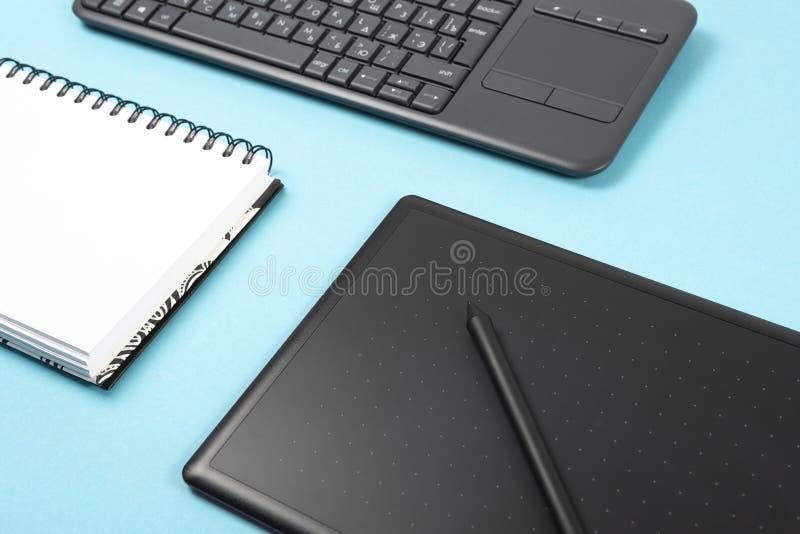 Grafiktablette und -tastatur auf einem blauen Hintergrund Raum für Text, Notizbuch lizenzfreie stockfotografie