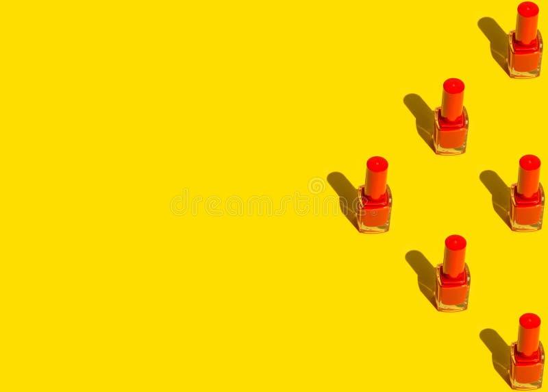 Grafisch patroon van rode die nagellakflessen in driehoek op gele achtergrond worden geschikt Pop-artstijl met schaduwen Maak omh stock afbeelding