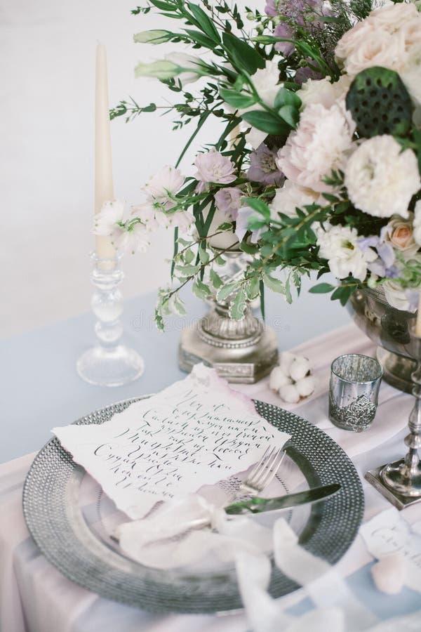 Grafische Künste von schönen Hochzeitskalligraphiekarten und von silberner Platte mit Tischbesteck stockfoto