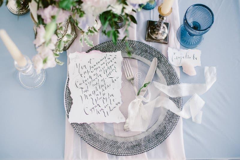 Grafische Künste von schönen Hochzeitskalligraphiekarten und von silberner Platte mit Tischbesteck lizenzfreies stockbild