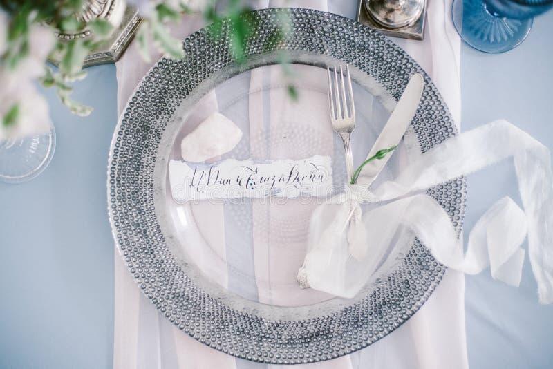 Grafische Künste von schönen Hochzeitskalligraphiekarten und von silberner Platte mit Tischbesteck stockbild
