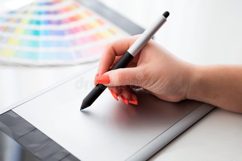 Grafische ontwerper die aan een digitale tablet en met palet werken royalty-vrije stock afbeeldingen