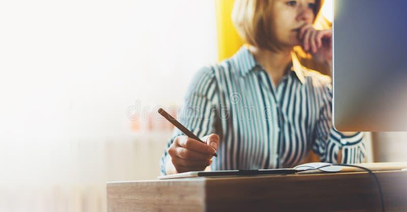 Grafische ontwerper die op kantoor met digitale naald aan achtergrondmonitorcomputer bij nacht werken, hipster manager die appara stock afbeelding