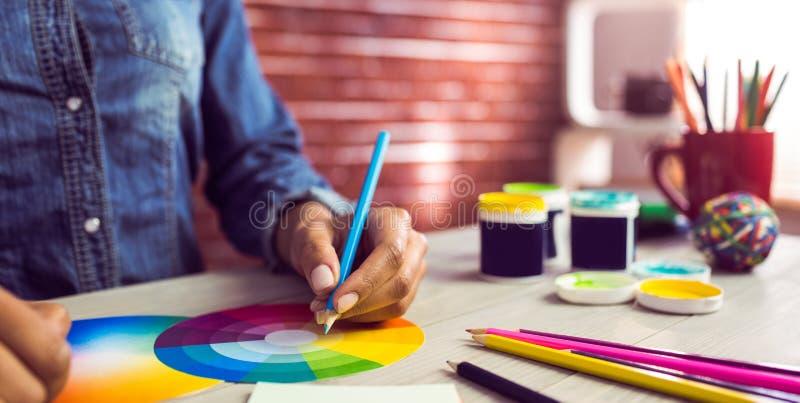 Grafische ontwerper die op kleurengrafiek trekken stock foto's
