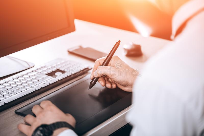 Grafische ontwerper` s werkruimte Hand op pentablet Jonge slimme mens in het bureau De vrije zwarte ruimte van het monitorexempla stock fotografie