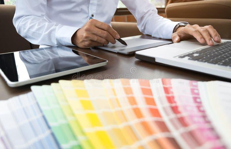Grafische ontwerperbaan met kleurengrafieken op een modern kantoor stock foto