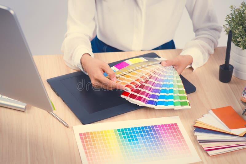 Grafische ontwerperholding op kleurengrafiek op het werk royalty-vrije stock afbeelding