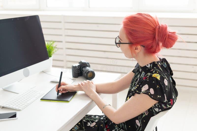 Grafisk formgivare, folkbegrepp - ung märkes- kvinnlig hipster med den grafiska minnestavlan som i regeringsställning arbetar royaltyfri foto