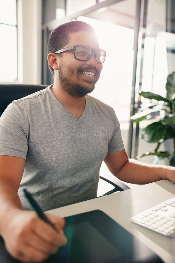Grafisk formgivare som använder den digitala diagramminnestavlan och skrivbordet royaltyfri fotografi