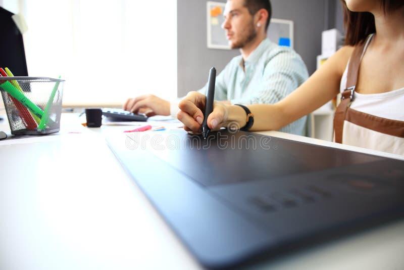 Grafisk formgivare som använder den digitala minnestavlan och datoren arkivfoton