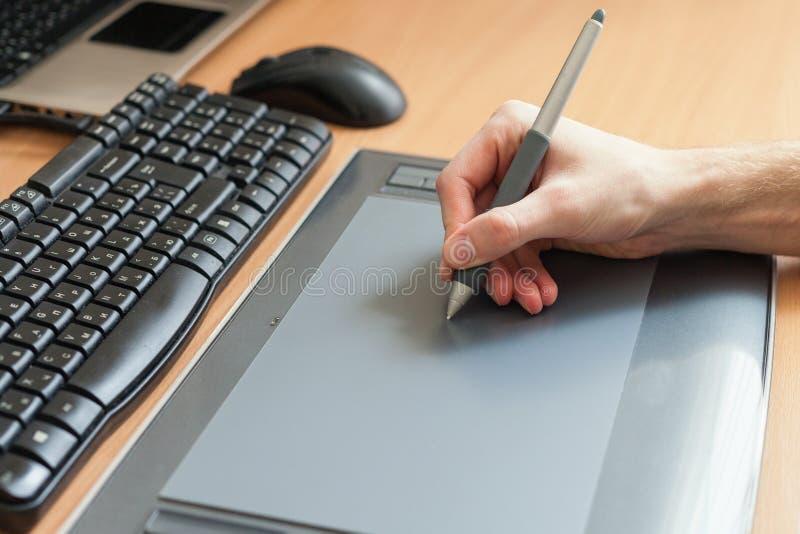 Grafisk formgivare som använder den digitala minnestavlan och datoren i kontoret royaltyfria bilder