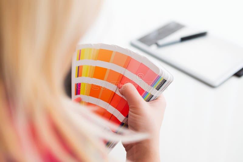 Grafisk formgivare som arbetar med pantonepaletten arkivfoton