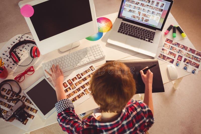 Grafisk formgivare som arbetar på skrivbordet royaltyfri fotografi
