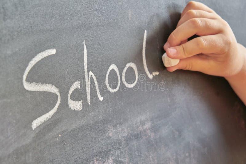 Grafisk framställning av ordet, skola som är skriftlig med krita på svart tavla arkivbilder