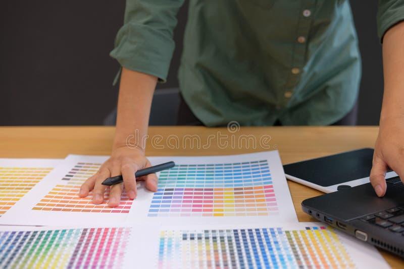 grafisk inreformgivare som arbetar med datoren & väljer färg royaltyfria foton