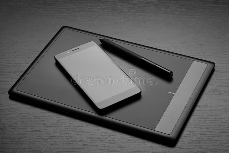 Grafisk minnestavla med en sakkunnig penna-som nålen och smartphonen på en trätabell royaltyfria foton