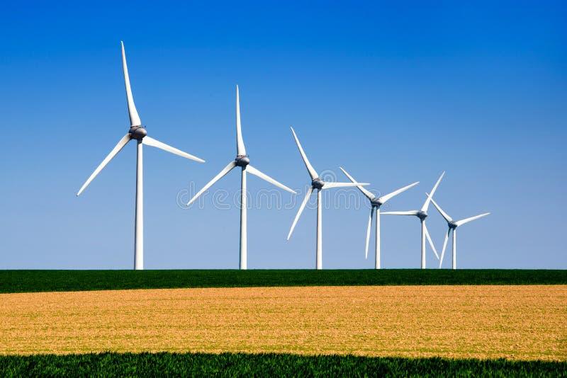 Grafiskt modernt landskap av vindturbiner arkivfoton