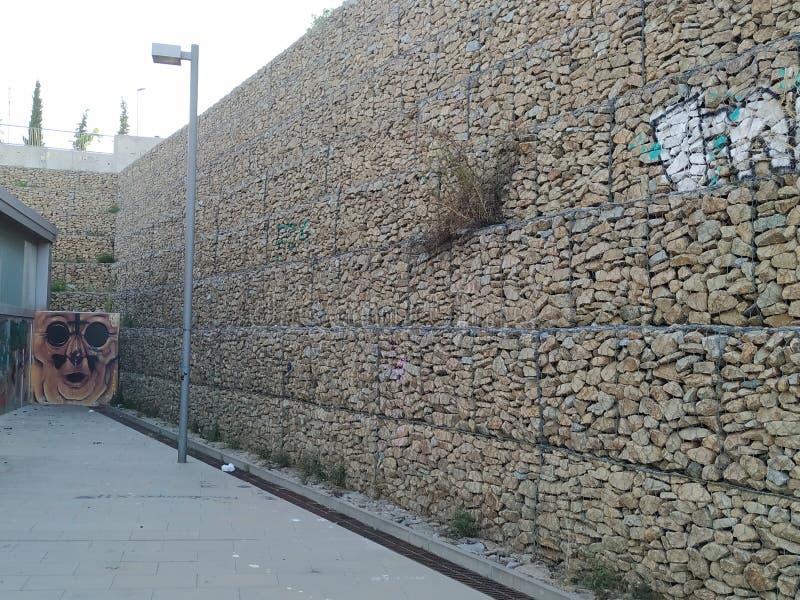 Grafities como uma arte urbana, parede construída com pedras imagem de stock