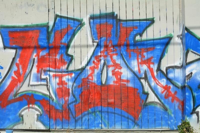 Grafitii and Urban Art in Portland, Oregon. This is red and blue graffiti on a building`s white wall in Portland, Oregon stock images