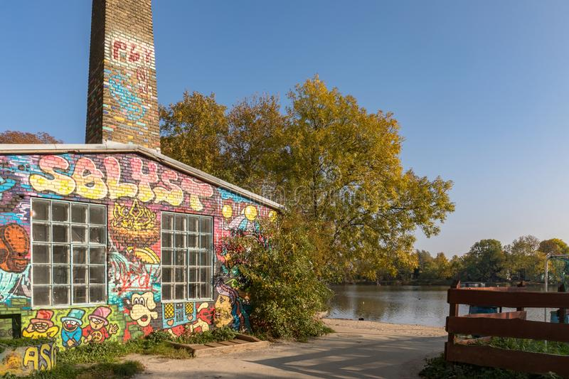 COPENHAGEN, DENMARK - October 2018: Building with grafitti by the canal in Freetown Christiania, a self-proclaimed. Grafitti-covered building by the beach stock photo