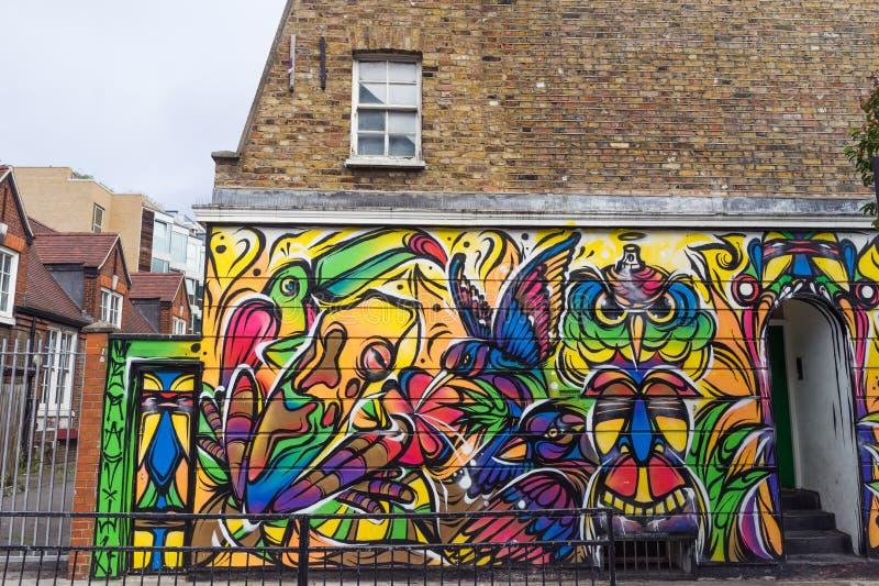 Grafitti målar den konst färgade väggen i London, England royaltyfri foto