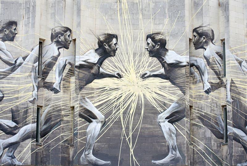 Grafitti på väggen som flyr folk arkivbilder