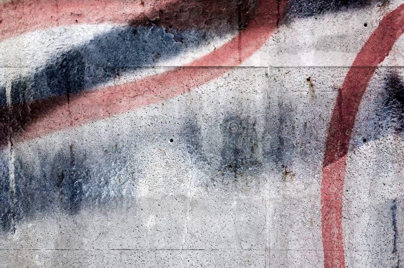 Grafittifragment över den gamla gråa betongväggen royaltyfri bild
