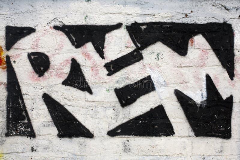 Grafittikonst på en ensam tegelstenvägg royaltyfri foto