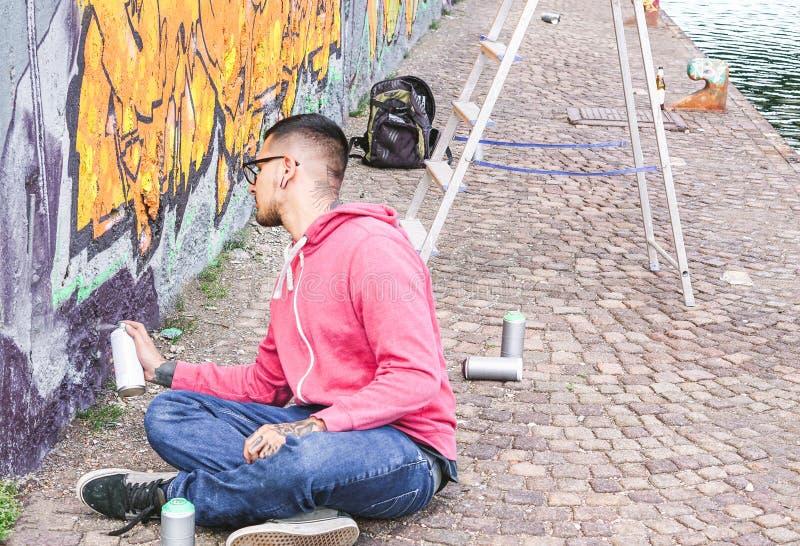 Grafittis coloridos em uma parede sob a ponte - homem urbano da pintura do artista da rua que executa com os murales imagens de stock