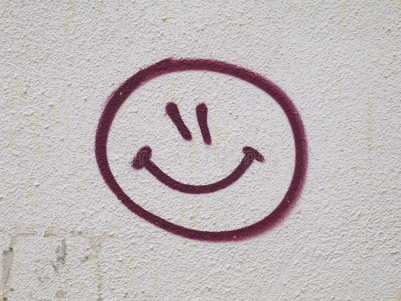 Grafittis da cara do smiley tirados na parede foto de stock